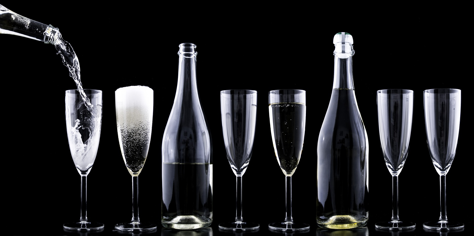 a line up of two champagne glasses, a champagne bottle, two glasses, champagne, two glasses, with champagne being poured into the first glass on the left