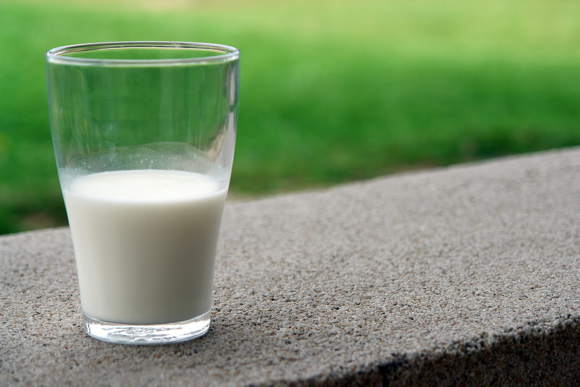 a half full glass of milk sitting on an outdoor wall