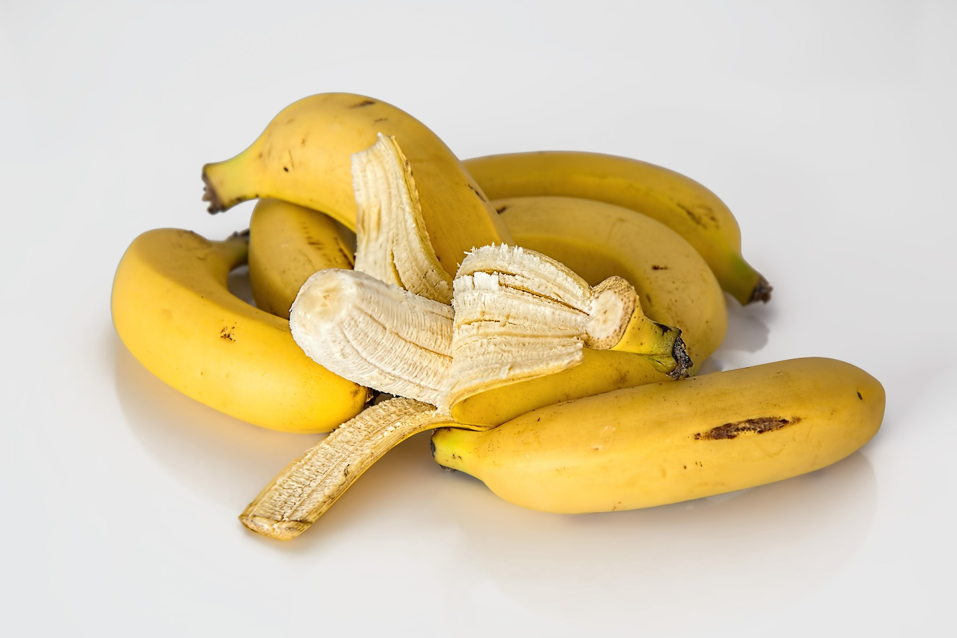 several bunches of bananas bunched together with one banana partly open in the middle