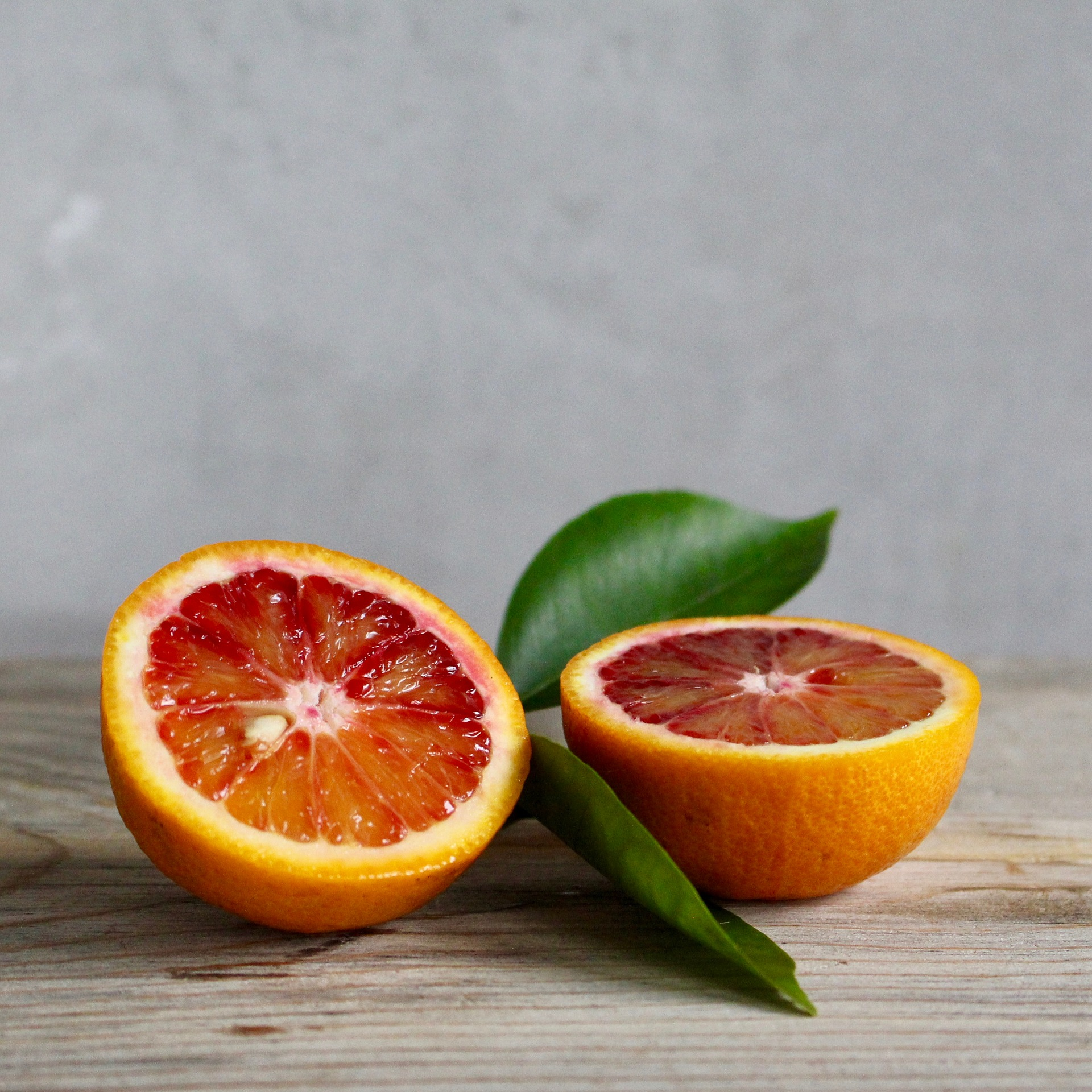 two blood oranges with garnish leaves in between