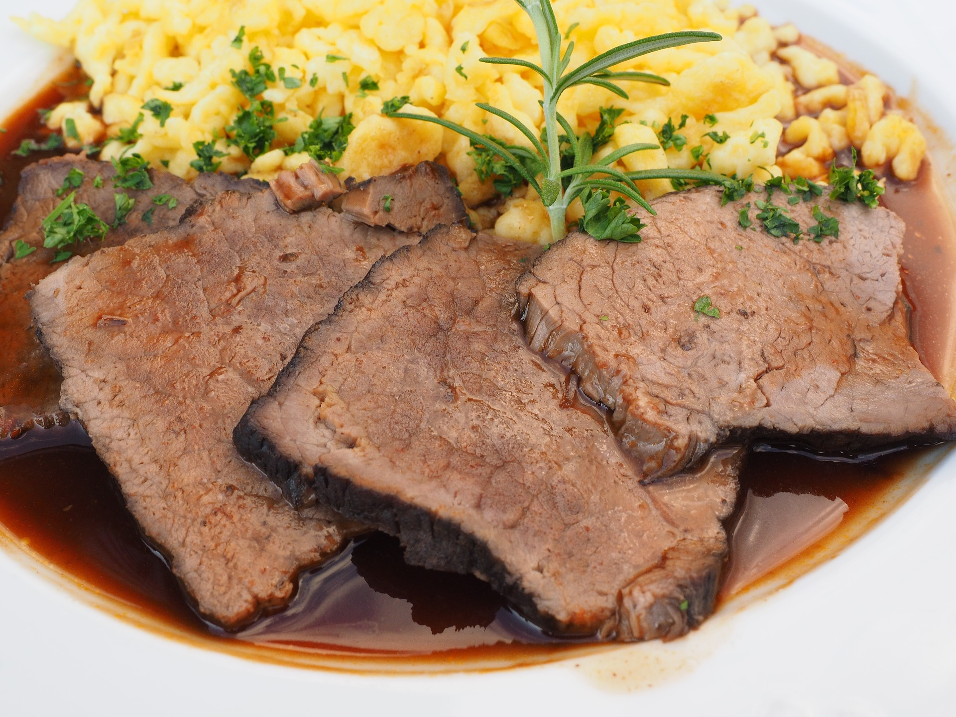 sliced pot roast on a plate with mac and cheese behind it