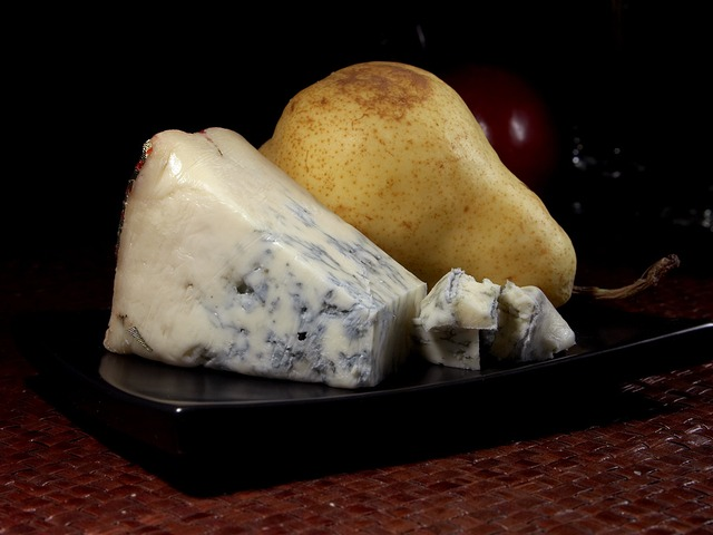a hunk of Gorgonzola cheese next to a pear