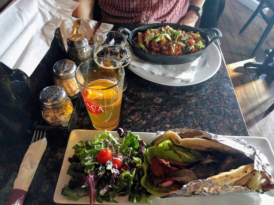 at a restaurant, a salad with a gyro and beer, the other person has some kind of dish in a skillet and also a beer
