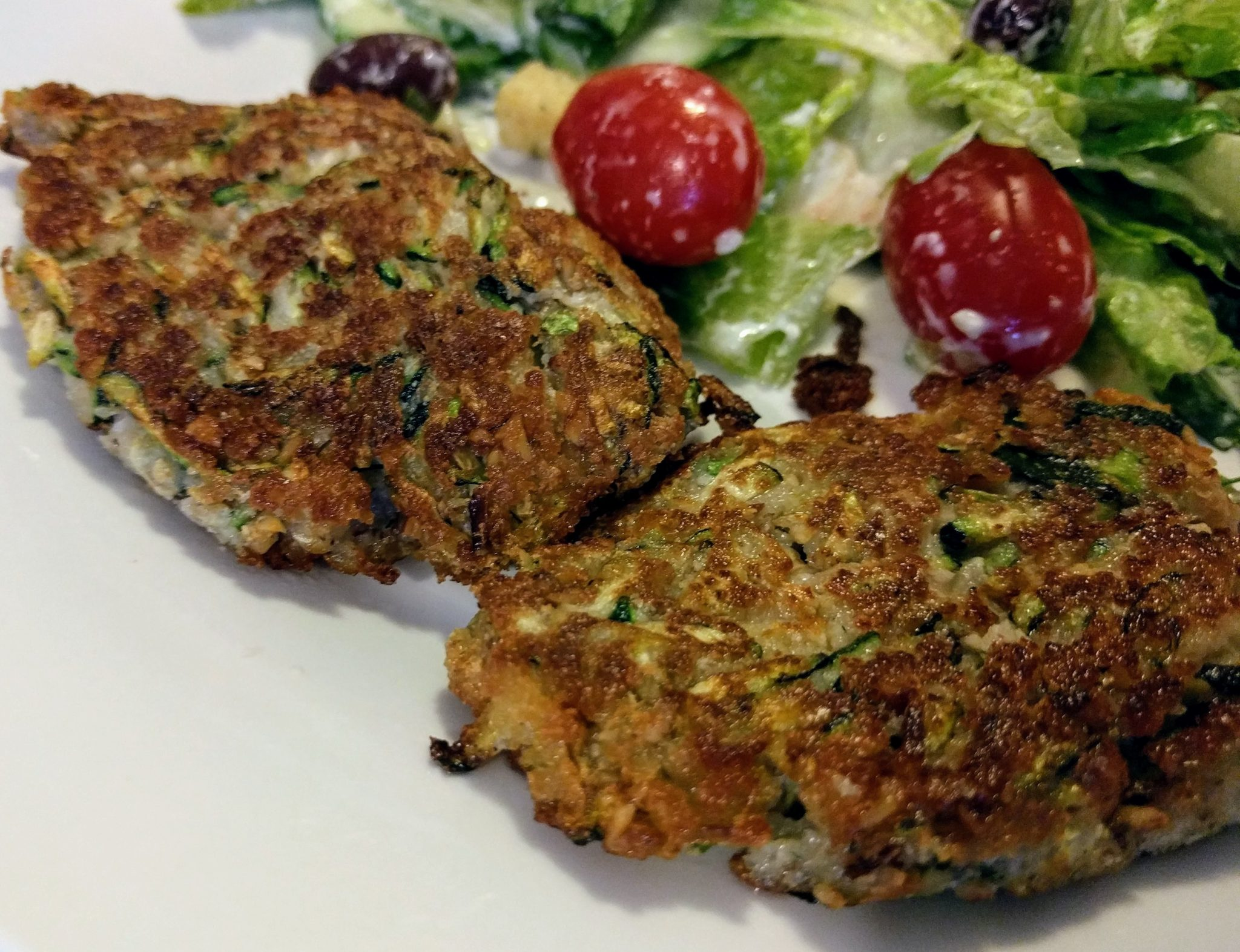 two zucchini fritters with a salad with lettuce and cherry tomatoes in the background